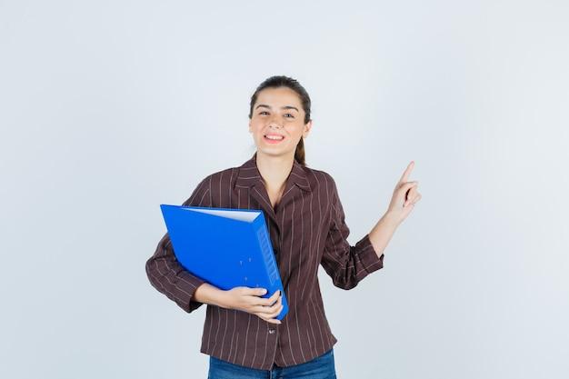 Señorita en camisa, jeans sosteniendo una carpeta, apuntando hacia arriba y mirando feliz, vista frontal.