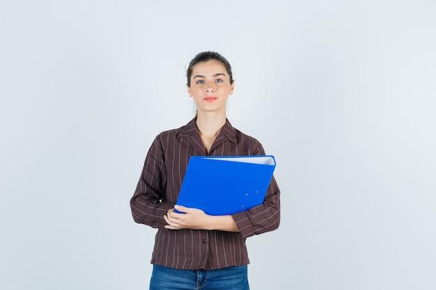 Señorita en camisa, jeans sosteniendo una carpeta, mirando a la cámara y mirando seria, vista frontal.