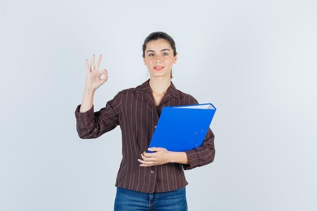 Señorita en camisa, jeans sosteniendo una carpeta, mostrando un gesto bien y mirando pensativo, vista frontal.