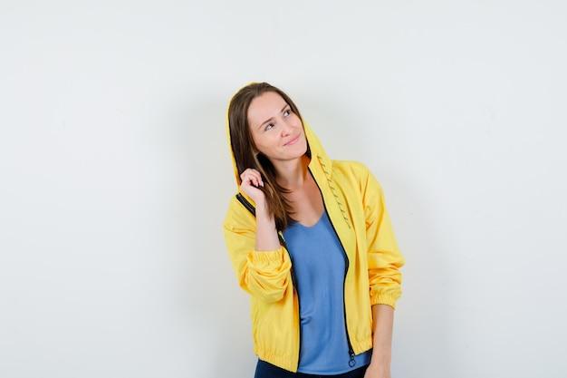 Señorita en camiseta, chaqueta posando mientras mira hacia arriba y parece soñadora