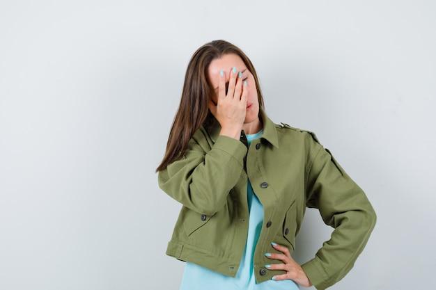Señorita en camiseta, chaqueta que cubre la cara con la mano mientras mantiene la mano en la cadera y parece olvidadizo, vista frontal.