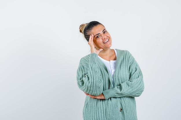 Señorita en camiseta, chaqueta sosteniendo la mano en la sien y mirando alegre