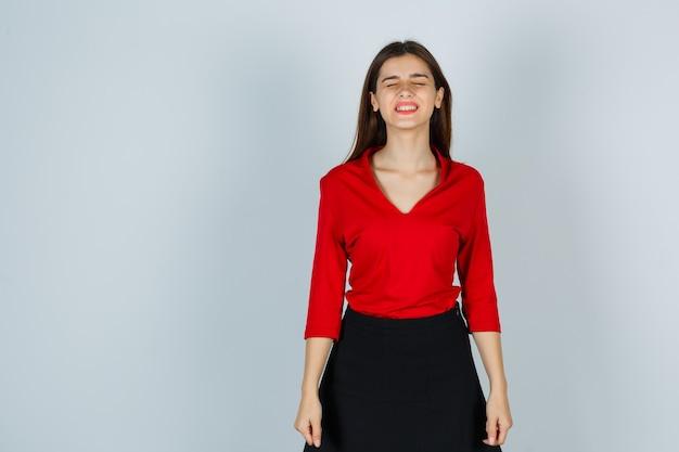 Señorita cerrando los ojos en blusa roja, falda y mirando esperanzado