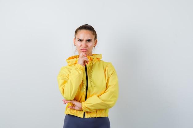 Señorita en chaqueta amarilla apoyando la barbilla en la mano y mirando seria, vista frontal.