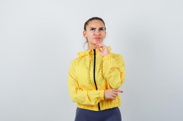 Señorita de chaqueta amarilla con la mano debajo de la barbilla y mirando pensativo, vista frontal.