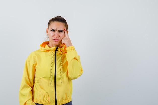 Señorita en chaqueta amarilla manteniendo el dedo en la sien y mirando disgustado, vista frontal.