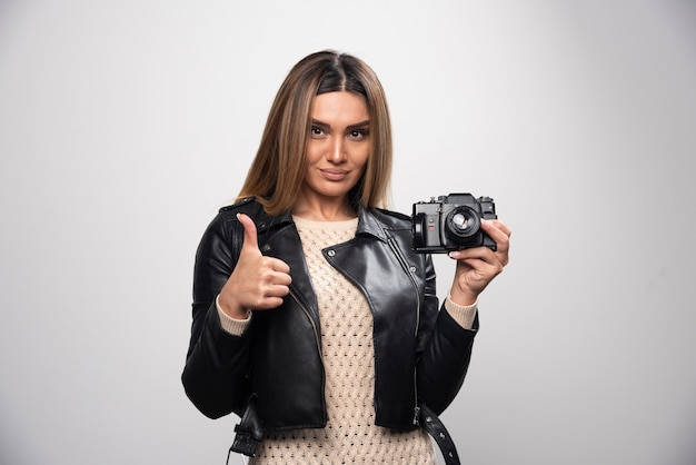 Señorita en chaqueta de cuero negro tomando fotos con cámara de manera positiva y sonriente.
