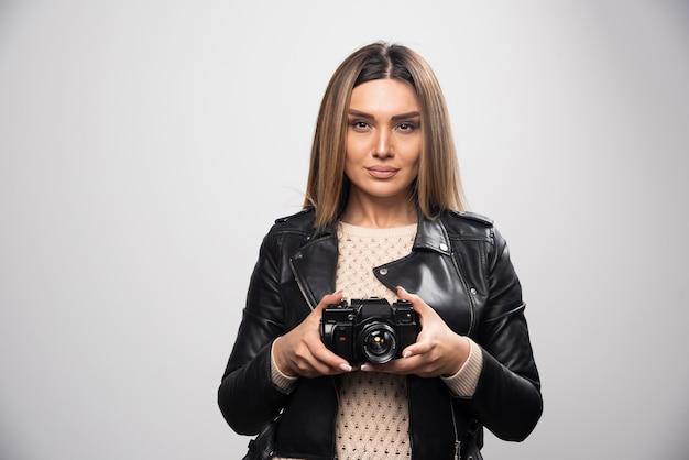Señorita en chaqueta de cuero negro tomando fotos con la cámara de manera seria y profesional.