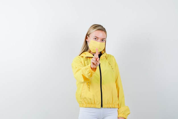 Señorita con chaqueta, pantalones, máscara que muestra un gesto de un minuto y una vista frontal sensata.