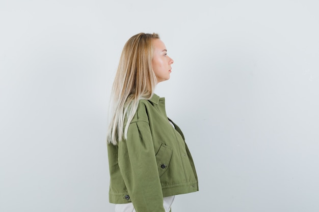 Señorita con chaqueta, pantalones mirando a otro lado y mirando enfocado.
