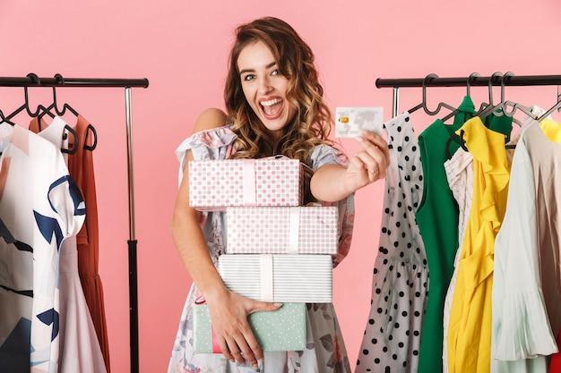 Señorita con compra de pie en la tienda cerca de perchero y sosteniendo una tarjeta de crédito aislada en rosa