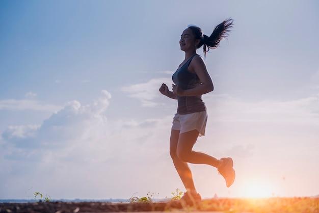 Señorita corriendo en un camino rural durante la puesta de sol