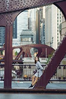 Señorita cruzando el puente de la ciudad