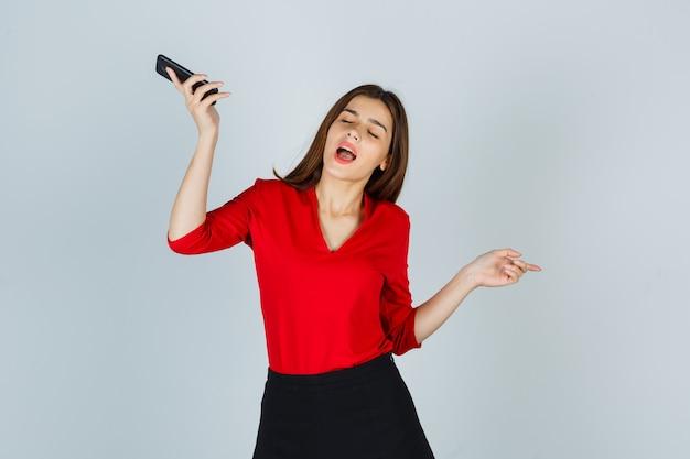 Señorita disfrutando mientras sostiene el teléfono móvil en blusa roja, falda y mirando divertido
