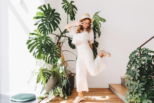 Señorita divertida en pantalones de moda de pie sobre una pierna y mostrando el signo de la paz con una sonrisa