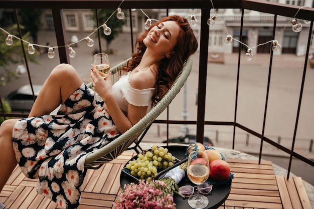Señorita en falda floral sostiene copa de champán y posa en la terraza