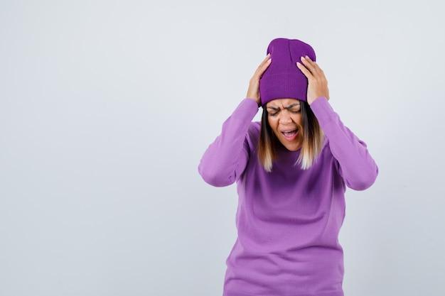 Señorita con las manos en la cabeza en suéter morado, gorro y mirando molesto. vista frontal.
