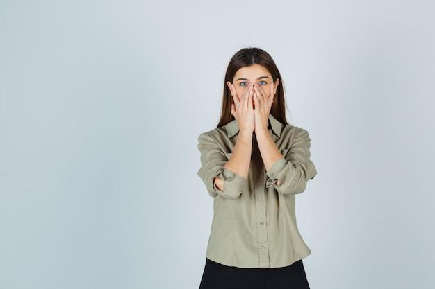 Señorita manteniendo las manos en la cara en camisa, falda y mirando decepcionado
