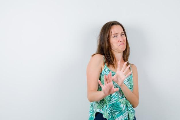 Señorita manteniendo las manos para defenderse en blusa y mirando asustada. vista frontal.
