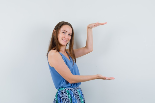 Señorita mostrando cartel de gran tamaño en blusa azul, falda y mirando contento, vista frontal.