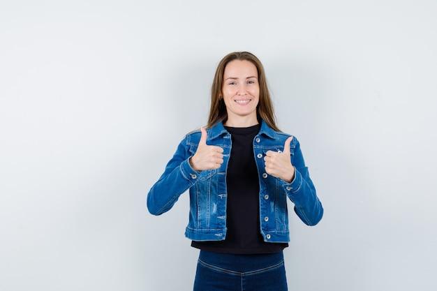 Señorita mostrando doble pulgar hacia arriba en camisa, chaqueta y mirando confiado, vista frontal.