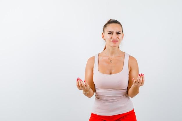 Señorita mostrando gesto italiano en camiseta beige y mirando inquieto