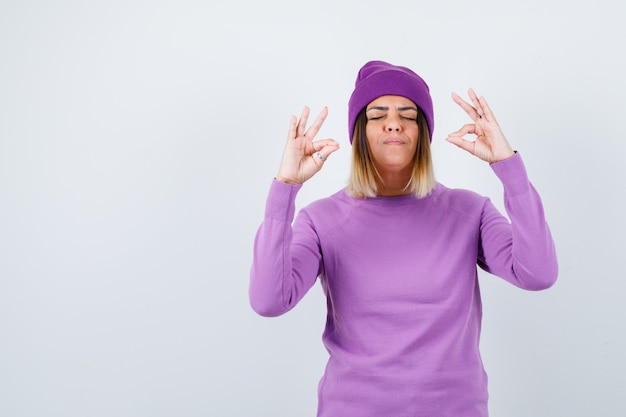 Señorita mostrando gesto de meditación en suéter morado, gorro y mirando pacífica, vista frontal.