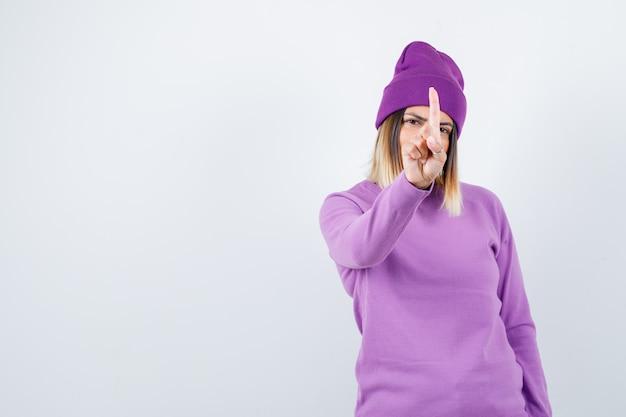 Señorita mostrando un gesto de minuto en suéter morado, gorro y mirando confiado. vista frontal.
