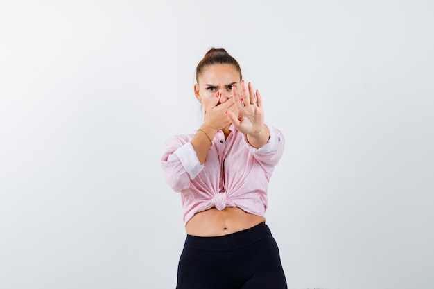 Señorita mostrando gesto de parada en camisa, pantalones y mirando asustado