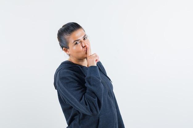 Señorita mostrando gesto de silencio en chaqueta y mirando tranquilo