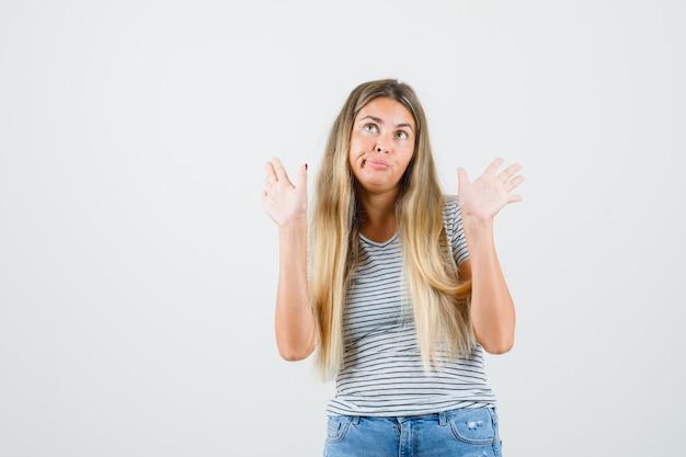 Señorita mostrando no sé gesto en camiseta y mirando perezoso, vista frontal.