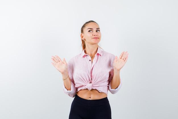 Señorita mostrando palmas en gesto de rendición en camisa, pantalones y mirando confiado