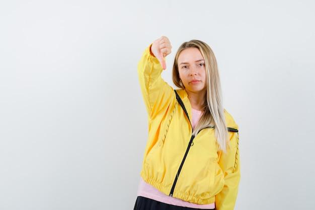 Señorita mostrando el pulgar hacia abajo en camiseta, chaqueta y mirando confiado