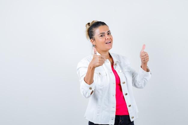 Señorita mostrando los pulgares para arriba en camiseta, chaqueta blanca y mirando complacido, vista frontal.