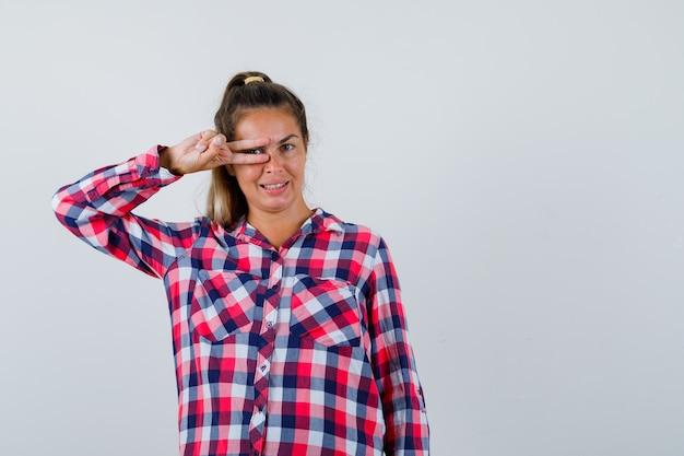Señorita mostrando el signo v en el ojo con camisa a cuadros y mirando feliz, vista frontal.