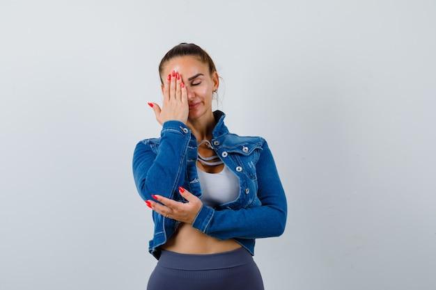 Señorita en la parte superior, chaqueta de mezclilla cubriendo los ojos con la mano y con aspecto cansado, vista frontal.