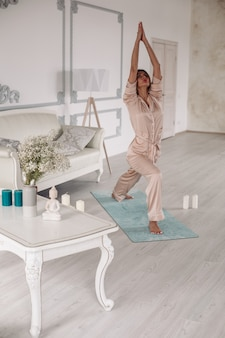 Señorita a partir de la mañana con ejercicios de yoga en el dormitorio