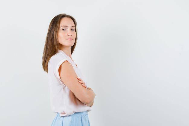 Señorita de pie con los brazos cruzados en camiseta, falda y mirando confiada. .