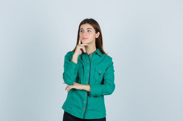 Señorita poniendo el dedo para apuntalar la barbilla en camisa verde y mirando pensativo, vista frontal.