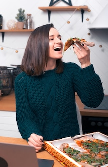 La señorita que acaba de recibir su pizza ordenada está comiendo una porción.