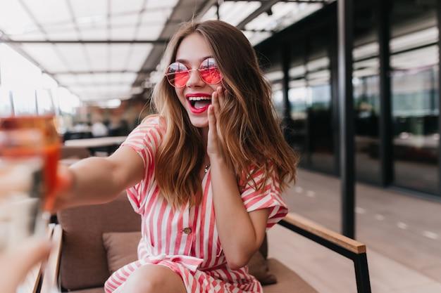 Señorita refinada en gafas de sol celebrando algo en la cafetería. filmación en interiores de una hermosa niña sonriente viste un vestido de verano a rayas.