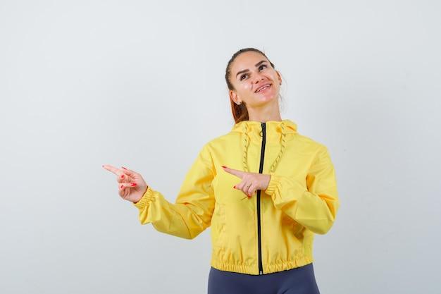 Señorita señalando a un lado, mirando hacia arriba con chaqueta amarilla y luciendo soñadora. vista frontal.