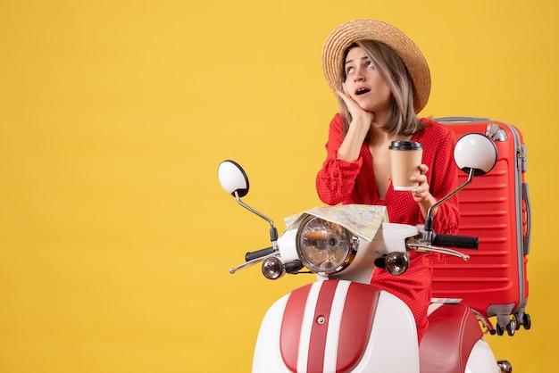 Señorita sorprendida en vestido rojo sosteniendo una taza de café cerca del ciclomotor