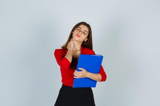 Señorita sosteniendo la carpeta mientras mantiene la mano en el cuello en blusa roja