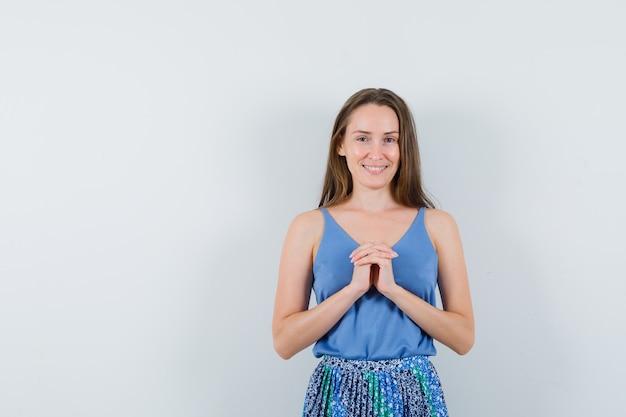 Señorita sosteniendo los dedos entrelazados en el pecho en camiseta, falda y luciendo esperanzada. vista frontal.