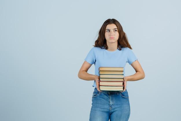 Señorita sosteniendo libros en camiseta, jeans y mirando insatisfecho. vista frontal.