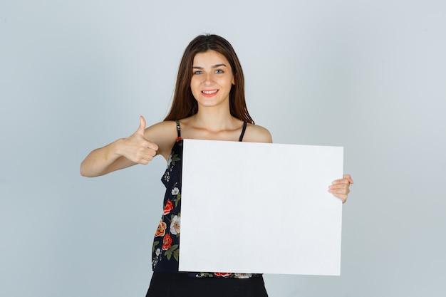Señorita sosteniendo un lienzo en blanco, mostrando el pulgar hacia arriba en blusa, falda y mirando feliz. vista frontal.