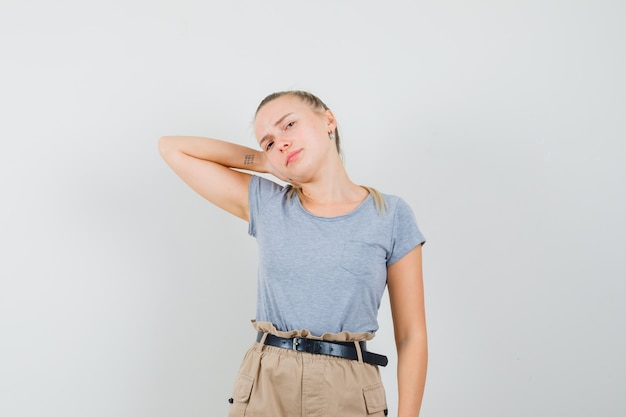 Señorita sosteniendo la mano en el cuello en camisetas y pantalones y mirando descontento