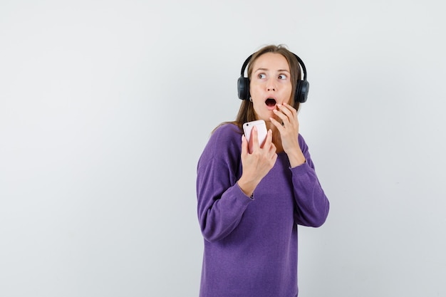 Señorita sosteniendo teléfono móvil en camisa violeta y mirando sorprendido, vista frontal.