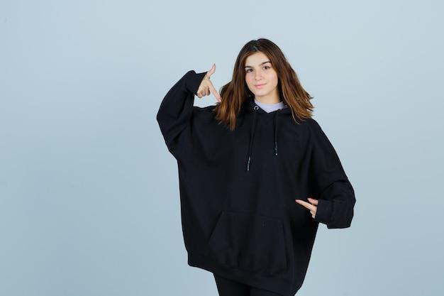Señorita en sudadera con capucha de gran tamaño, pantalones apuntando a sí misma y luciendo orgullosa, vista frontal.